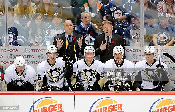 Assistant Coach Rick Tocchet and Head Coach Mike Johnston of the Pittsburgh Penguins react to action on the ice during second period play between the...