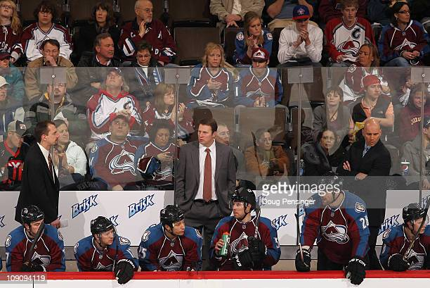 Assistant coach Steve Konowalchuk head coach Joe Sacco and assistant coach Sylvain Lefebvre of the Colorado Avalanche stand behind the players on the...