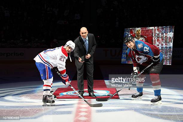 Assistant coach Sylvain Lefebvre middle of the Colorado Avalanche holds the puck for a ceremonial drop between Adam Foote and Brian Gionta of the...