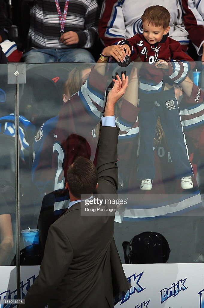 Assistant coach Tim Army of the Colorado Avalanche gives a puck to a young fan as they face the Anaheim Ducks during preseason action at Pepsi Center on September 18, 2013 in Denver, Colorado. The Ducks defeated the Avalanche 2-1.