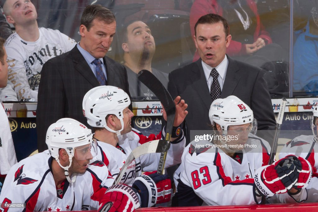 Assistant coach Tim Hunter (L) and head coach Adam Oates (R) of the Washington Capitals talk to their players during an NHL game against the Ottawa Senators at Scotiabank Place on January 29, 2013 in Ottawa, Ontario, Canada.