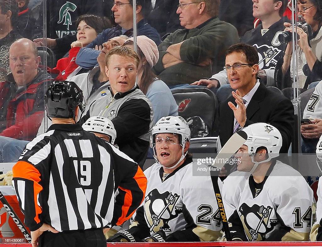 Assistant coach Tony Granado of the Pittsburgh Penguins has a discussion with referee Gord Dwyer against the New Jersey Devils during the game at the Prudential Center on February 9, 2013 in Newark, New Jersey.