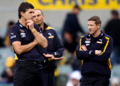 Assistant coaches Justin Longmuir and Scott Burns look on as players warm up before the start of the round 21 AFL match between the West Coast Eagles...