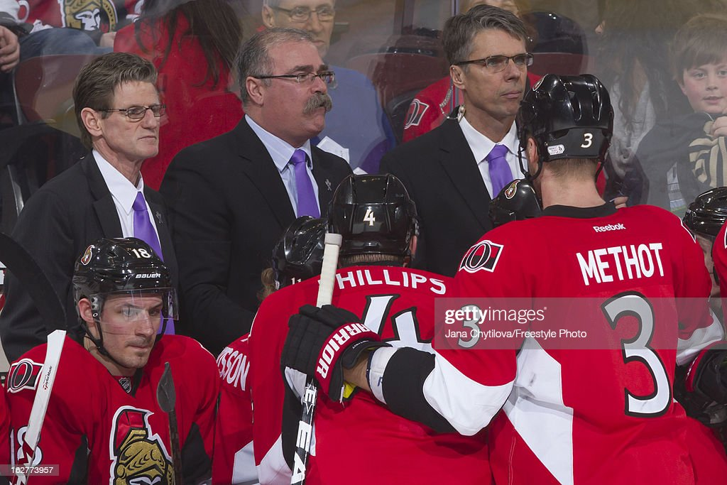 Assistant coaches Mark Reeds and Dave Cameron and head coach Paul MacLean of the Ottawa Senatorswear purple ties in support of Do It For Daron during...