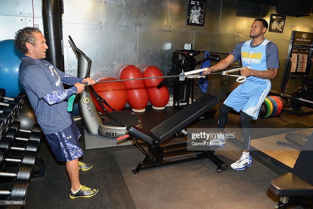 Assistant Coach/Strength and Conditioning Coach Steve Hess works with Andre Iguodala #9 of the Denver Nuggets prior to practice on October 24, 2012 at the Pepsi Center in Denver, Colorado.