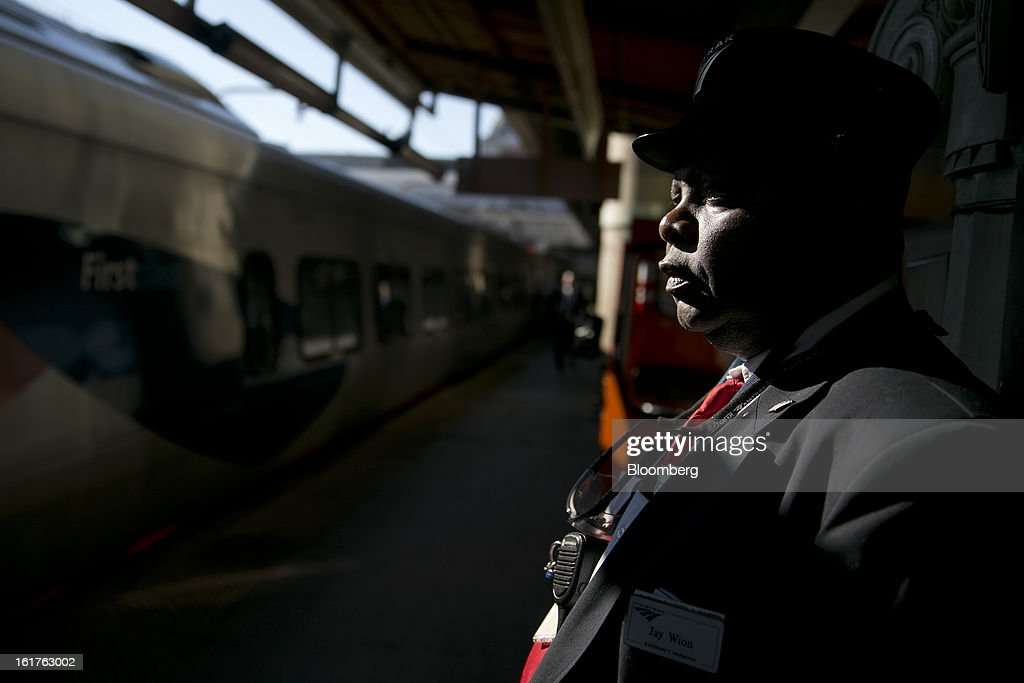 Assistant conductor Jerry Wion waits to assist passengers on the Amtrak Acela platform at Union Station in Washington, D.C., U.S., on Friday, Feb. 15, 2013. Amtrak, the U.S. long-distance passenger railroad and federally subsidized since its beginning 41 years ago, last month reported its lowest operating loss in nearly four decades, announcing the passenger rail company had reduced its total operating loss by 19 percent compared to the previous year. Photographer: Andrew Harrer/Bloomberg via Getty Images