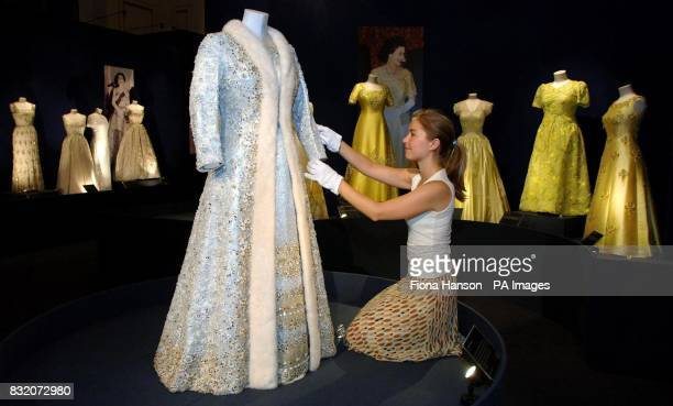 Assistant Curator Melanie Edwards with a gown designed by Norman Hartnell in 1972 of pearl sequin and diamante embroidered tissue with a mink trimmed...