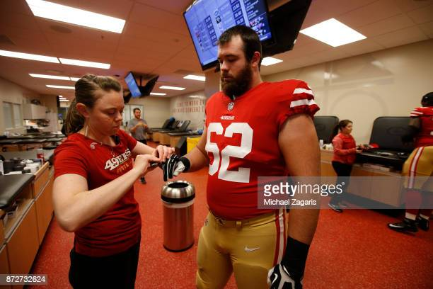 Assistant Head Athletic Trainer Laura Schnettgoecke of the San Francisco 49ers tapes of Erik Magnuson in the locker room prior to the game against...
