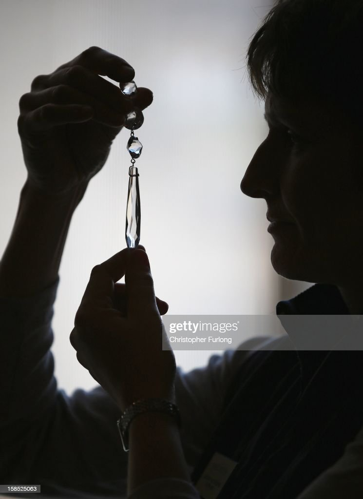 Assistant House Keeper at Chatsworth House, Janet Bitton inspects a crystal drop during the process of deep cleaning a regency cut glass chandlier at the stately home on December 18, 2012 in Chatsworth, England. The Derbyshire stately home of the Duke and Duchess of Devonshire is currently undergoing it's annual deep clean and conservation work on the second floor. The historic house has over 300 rooms, 17 staircases, 459 windows and requires an army of specialists to keep it in pristine condition. The conservation work continues through the winter and is completed by 10th March when the house fully re-opens.