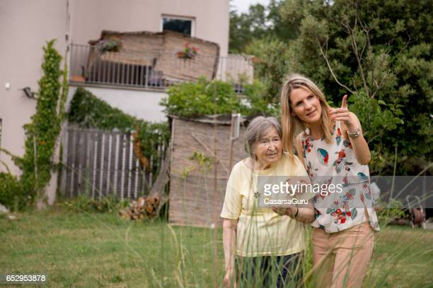 Assistant In The Nursery Home Have A Walk With Senior Woman In The Garden