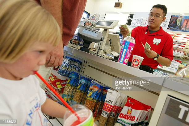 Assistant manager Engel Mozo rings up a sale as 3yearold Samantha Krass sips on her Slurpee at a 7Eleven store on July 18 2002 in Pembroke Pines...