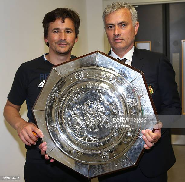 Assistant Manager Rui Faria and Manager Jose Mourinho of Manchester United pose with the Community Shield trophy in the dressing room after the FA...