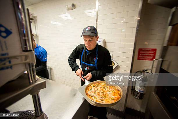 Assistant Manager Tyler Peterson unloads a pizza from an oven at a Domino's Pizza Inc 'pizza theater' location in Jersey City New Jersey US on Friday...
