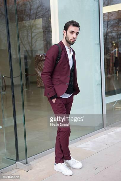 Assistant of Stephane Rolland Maxim Houvion wears a Louis Vuitton back pack Adidas trainers HM suit Cos shirt Akris vest on day 3 of Paris Haute...