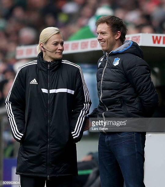 Assistant referee Bibiana Steinhaus smiles with head coach Julian Nagelsmann of Hoffenheim during the Bundesliga match between Werder Bremen and 1899...