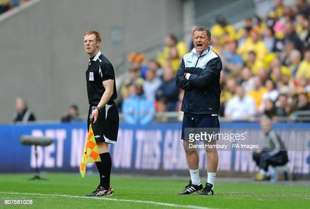 Assistant referee Carl Fitch with Oxford United manager Chris Wilder on the touchline during the match