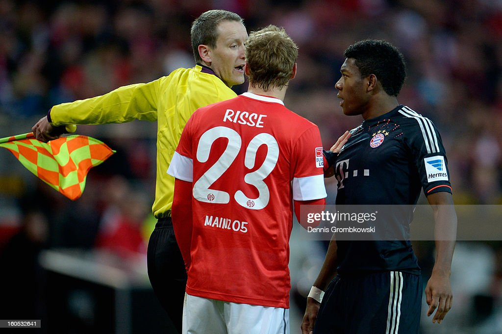 Assistant referee Norbert Grudzinski stops <a gi-track='captionPersonalityLinkClicked' href=/galleries/search?phrase=Marcel+Risse&family=editorial&specificpeople=4331527 ng-click='$event.stopPropagation()'>Marcel Risse</a> of Mainz and <a gi-track='captionPersonalityLinkClicked' href=/galleries/search?phrase=David+Alaba&family=editorial&specificpeople=5494608 ng-click='$event.stopPropagation()'>David Alaba</a> of Bayern from arguing during the Bundesliga match between 1. FSV Mainz 05 and FC Bayern Muenchen at Coface Arena on February 2, 2013 in Mainz, Germany.