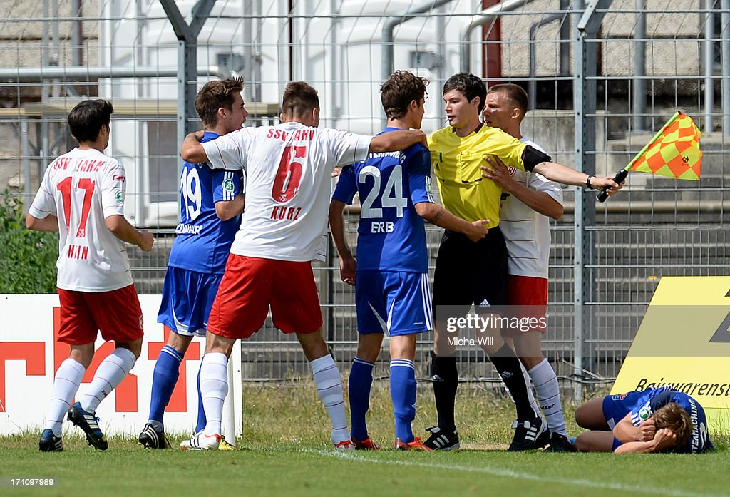 assistant referee Philipp Lehmann (3rd R) tries to clear a scuffle during the Third League match between Jahn Regensburg and SpVgg Unterhaching at Jahnstadion on July 20, 2013 in Regensburg, Germany.