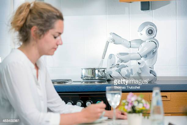 A assistant robot cooks for a single woman while she sits alone at the table and eats on August 01 2013 in Berlin Germany