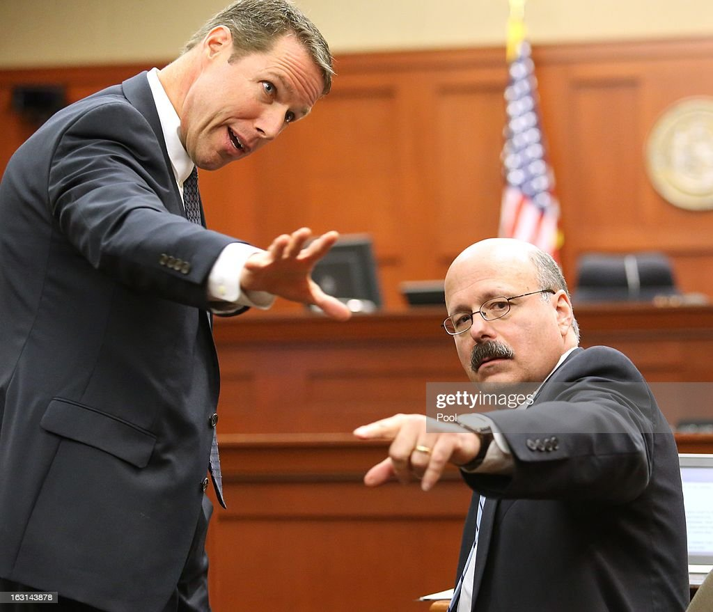 Assistant state attorneys John Guy and Bernie de la Rionda confer during a status hearing in the Trayvon Martin case, in Seminole circuit court March 5, 2013 in Sanford, Florida. The defense lawyers were reportedly looking for more access to the FBI's investigation into possible civil rights violations in the shooting of Martin.