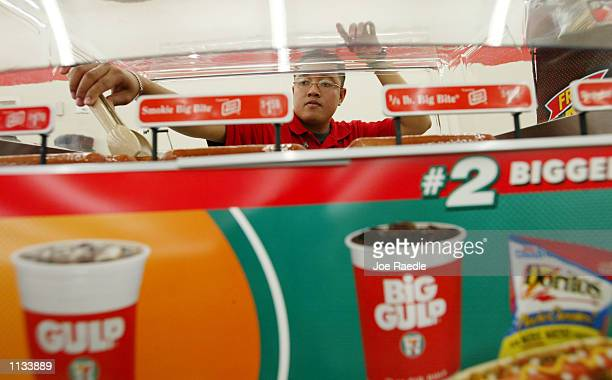Assistant store manager Engel Mozo turns the hot dogs on a grill at a 7Eleven store on July 18 2002 in Pembroke Pines Florida 7Eleven Inc the...