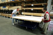 Assistant store manager Juan Ramos right assists Dennis Scheckenbach with his plywood purchase at a Lowe's home improvement store September 1 2005 in...
