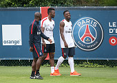 Assistantcoach of PSG Zoumana Camara JeanChristophe Bahebeck Serge Aurier leave the pitch following the first training session of the season for...