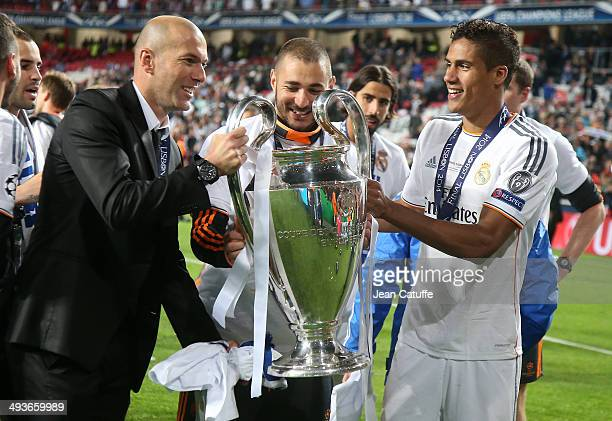 Assistantcoach of Real Madrid Zinedine Zidane Karim Benzema and Raphael Varane of Real Madrid hold the trophy after the UEFA Champions League final...