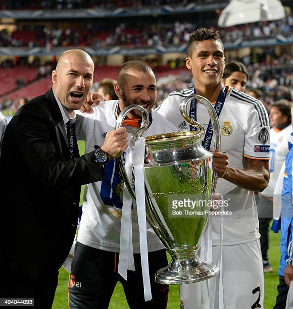 R assistantcoach of Real Madrid Zinedine Zidane Karim Benzema and Raphael Varane celebrate with the trophy after the UEFA Champions League Final...