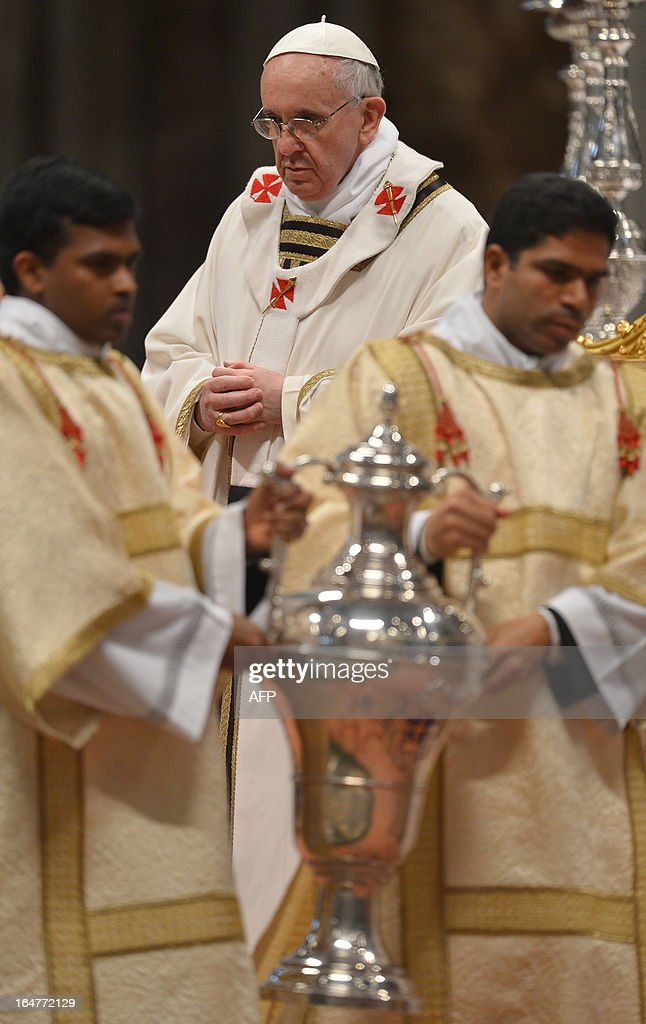 Assistants carry the amphora containing holy oil past Pope Francis during the Chrism mass on Holy Thursday on March 28, 2013 at the St Peter basilica at the Vatican.