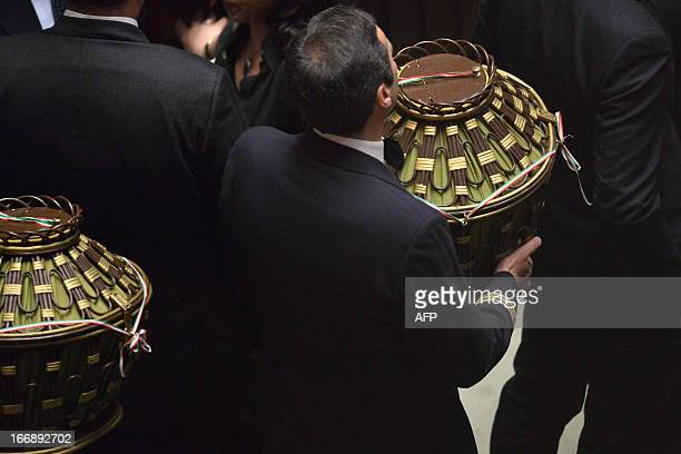 Assistants carry the urns after a vote during the election of the President of Italy on April 18 2013 at the Italian parliament in Rome While the...