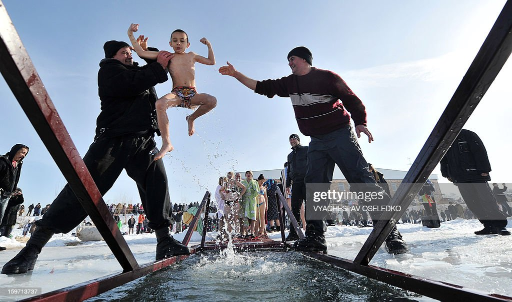Assistants help an Orthodox believer to take a bath in the icy waters of a lake in the village of Leninskoe about 20km from Bishkek on January 19, 2013 as part of Epiphany celebrations. For Christians, the Epiphany celebrates the baptism of Christ by John the Baptist in the river Jordan.
