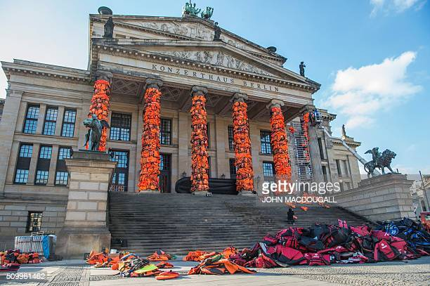 Assistants of Chinese artist Ai Weiwei decorate the columns of Berlin's Konzerthaus concert hall with lifejackets on February 13 as part of a...