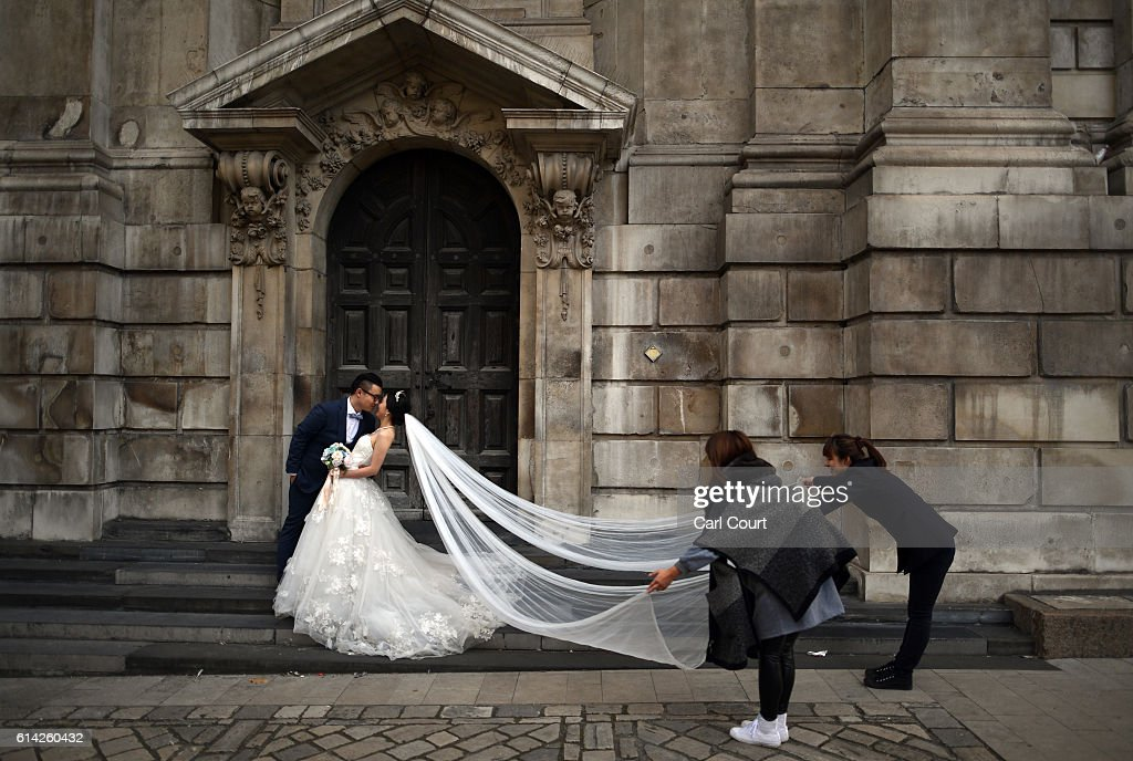 Assistants pull the train of the dress as bride-to-be, Echo Li and her fiance Charles Qian, pose during a pre-wedding photography shoot at St Paul's Cathedral, on October 11, 2016 in London, England. It's a Chinese custom for couples to have their wedding photos taken before they are married and on the wedding day the photos will be shown to guests on cards and big screens. Photography studios such as J.R Studios in east London have seen business boom as the capital has become increasingly popular as a location for pre-wedding photography thanks in part to its instantly recognisable landmarks.