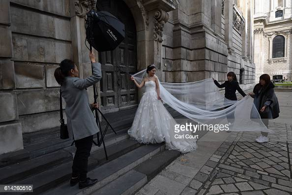Assistants pull the train of the dress as bridetobe Echo Li poses during a prewedding photography shoot at St Paul's Cathedral on October 11 2016 in...