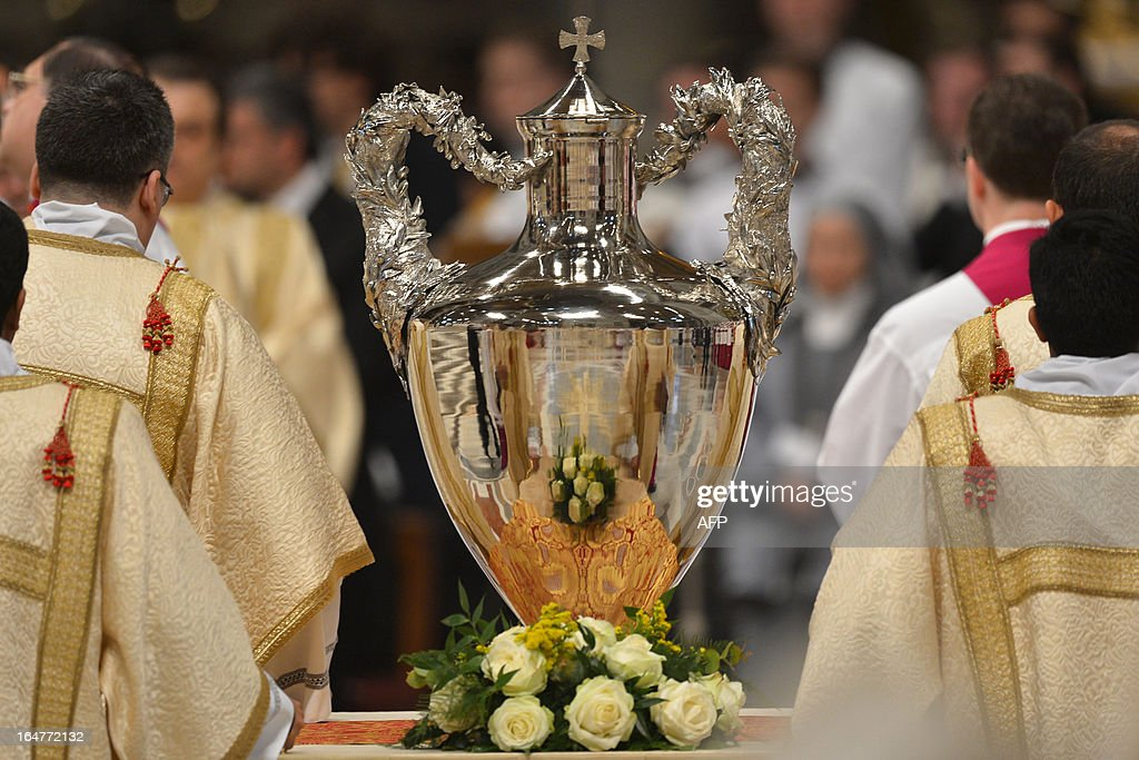 Assistants stand by the amphora containing holy oil past Pope Francis during the Chrism mass on Holy Thursday on March 28, 2013 at the St Peter basilica at the Vatican.
