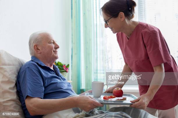 Assisted living – female caregiver helping senior man