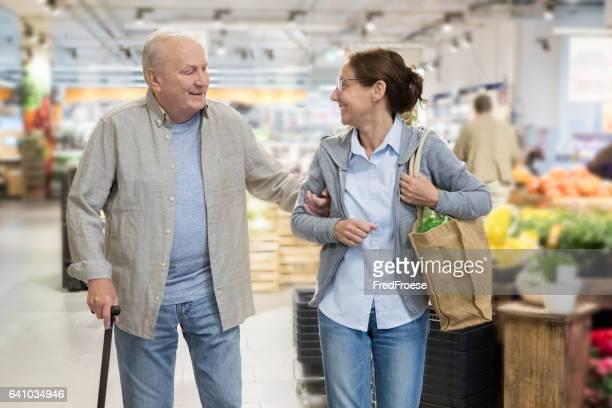Vida asistida-senior hombre con compras para el cuidador