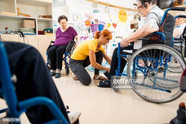 Assistent Helping Senior During Foot Massage In The Retirement Community