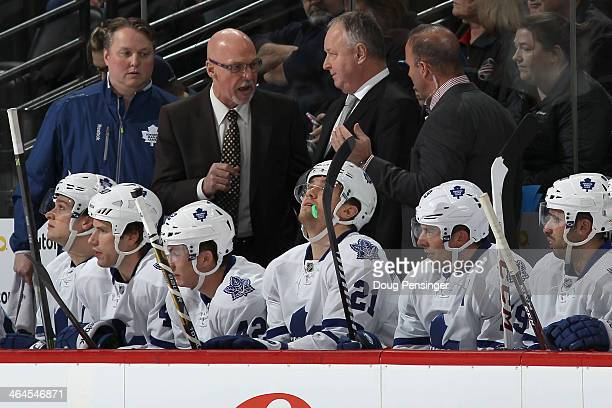 Assitant coach Dave Farrish head coach Randy Carlyle and assistant coach Greg Cronin confer on the bench as they face the Colorado Avalanche at Pepsi...