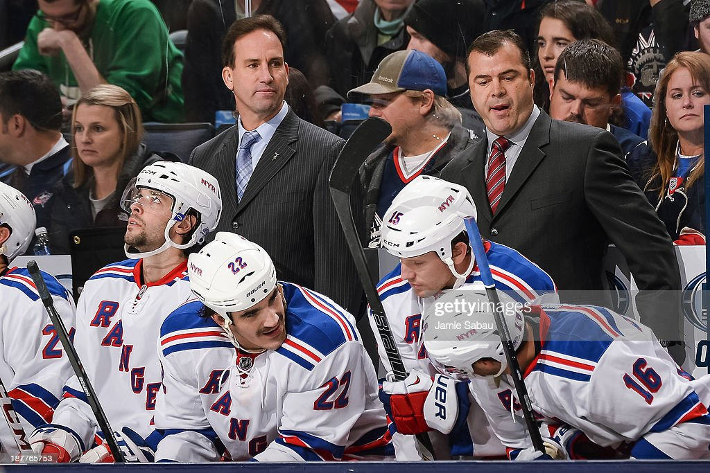 Associate Coach Scott Arniel, left, and Head Coach Alain Vigneault of the New York Rangers watch their team play the Columbus Blue Jackets on November 7, 2013 at Nationwide Arena in Columbus, Ohio.