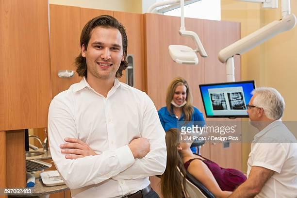 Associate dentist posing during patient consultation