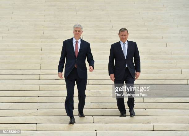 Associate Justice Neil M Gorsuch center left is accompanied by Chief Justice John Roberts as they walk down the steps of the US Supreme Court...