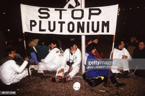 L'association Greenpeace deploie une banderole 'Stop Pollution' lors du chargement de plutonium sur un cargo japonais le 7 novembre 1992 à Cherbourg...