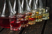 Assorted alcoholic cordials in glasses and decanters on dark wood background
