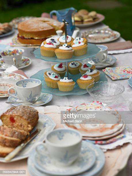 Assorted cakes and teacups laid out on table, outdoors, close-up