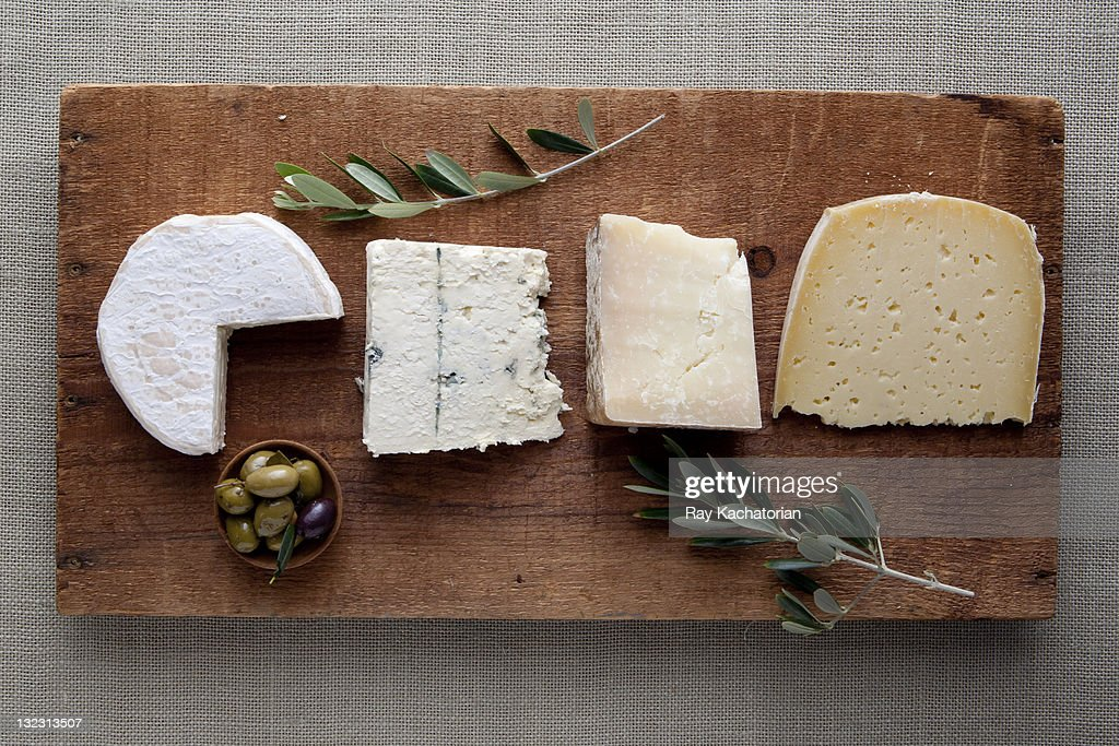 Assorted cheeses on wooden board.