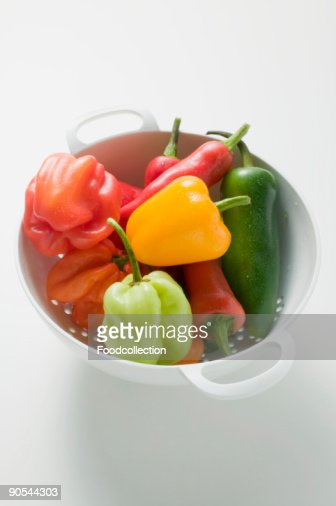 Assorted chillies in colander, close up, elevated view : Stock Photo