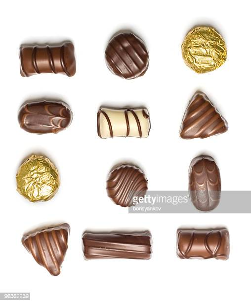 Assorted chocolates laid individually on white background