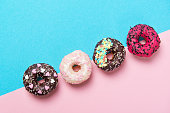 Four assorted colored donuts in a row, minimalism on a blue and pink background, top view